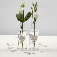 Un vase en verre décoré d'un coeur en bois fixé avec une ceinture en ruban de satin blanc