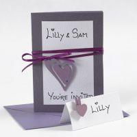 Une enveloppe et une invitation décorée d'un ruban en satin et un coeur
