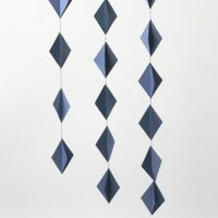 Des décorations à suspendre faites de diamants de papier cartonnés en 3D cousus ensemble