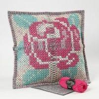 Un coussin décoré d'une rose brodé