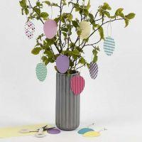 Des oeufs décoratifs à suspendre faits à partir de papier cartonné à motifs