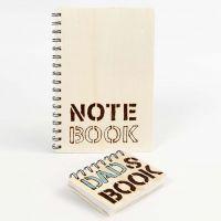 Un carnet de notes avec une couverture en bois, décoré avec des mots gravés