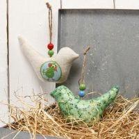 Un oiseau en tissu à suspendre, décoré avec du papier de découpage et des perles