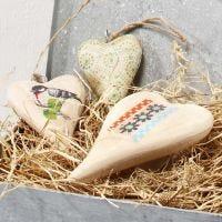 Un coeur en bois à suspendre décoré avec du papier de découpage