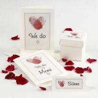 Une invitation de mariage et des décorations de table avec des coeurs d'empreintes digitales
