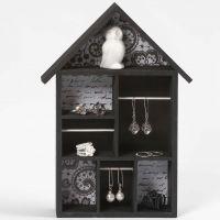 Un système d'étagères en forme de maison, peint en noir avec du papier de découpage et des bâtons transversaux pour suspendre des articles