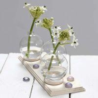 Un petit vase fait à partir d'une boule de verre debout sur une bague de rideau