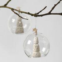 Un arbre de Noël d'argile blanche à l'intérieur d'une boule de verre