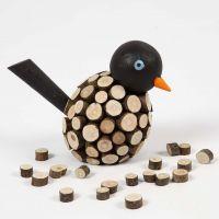 Un oiseau peint décoré de petits disques en bois avec écorce