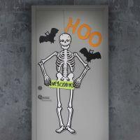 Un porte d'Halloween décorée d'un grand squelette et de chauves-souris