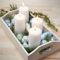 Un plateau avec quatre bougies et des boules de Noël en verre et en terre cuite peintes.