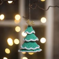 A Christmas tree crocheted from cotton yarn and gold yarn