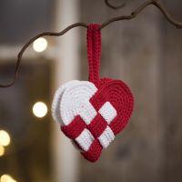 Un panier de Noël en forme de coeur, crocheté avec du fil de coton rouge et blanc