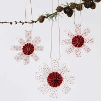 Des décoration à suspendre en bandes de papier vélin pour pliage étoiles décorées de paillettes et d'une rosette au milieu