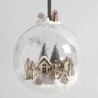 Un monde miniature en pâte Foam Clay et des figurines en bois à l'intérieur d'une boule de Noël