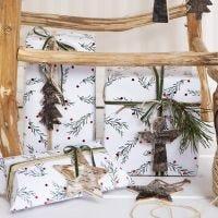 Emballage cadeau de Noël avec un motif de branches vertes, décoré d'un bout de chanvre naturel, d'un ruban et d'une étiquette cadeau en écorce d'arbre