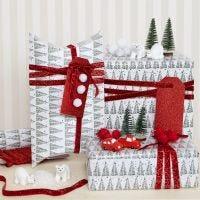 Du papier cadeau de Noël décoré avec des pompons et des figurines miniatures