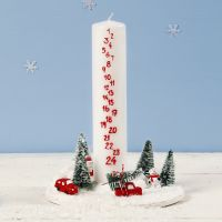 Une décoration avec une bougie de l'Avent entourée d'un monde de Noël miniature