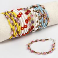 Un bracelet avec des fleurs faites en perles rocailles