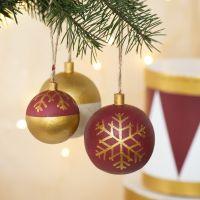 Des boules de Noël en bois décorées avec de la peinture acrylique et des feutres Plus Color