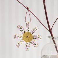 Une décoration à suspendre en bandes de papier étoiles et en papier pailletté