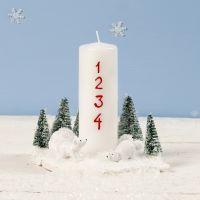 Une décoration de Noël avec une bougie, des ours polaires et des sapins de Noël miniatures