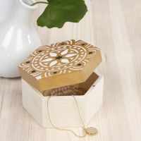Une boîte de rangement en bois décorée à l'aide d'un pochoir de motifs ethniques