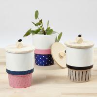 Une tasse décorée avec de la peinture pour porcelaine et un couvercle avec un perle en bois