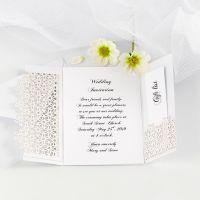 Une invitation de mariage pliée en deux decorée avec du papier cartonné à motif de dentelle