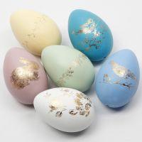 Oeufs de Pâques décorés avec du film décoratif placé sur des motifs de film adhésif