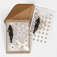 Une invitation avec une silhouette en papier cartonné, du papier cartonné au motif de dentelle et du papier vélin pour une première communion
