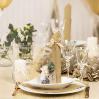 Des décorations de table dorées avec des fleurs en papier, des ballons, des serviettes pliées en forme de tours et des marque-places