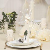 Des décorations de table blanc cassé avec des fleurs en papier, des ballons, des serviettes pliées en forme de tours et des marque-places