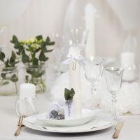 Des décorations de table blanches avec des fleurs en papier, des ballons, des serviettes pliées en forme de tours et des marque-places