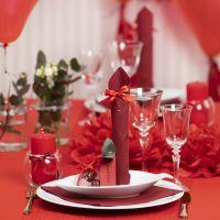 Des décorations de table rouges avec des fleurs en papier, des ballons, des serviettes pliées en forme de tours et des marque-places