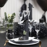 Des décorations de table noires avec des fleurs en papier, des ballons, des serviettes pliées en forme de tours et des marque-places