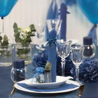 Des décorations de table bleu noir avec des fleurs en papier, des ballons, des serviettes pliées en forme de tours et des marque-places
