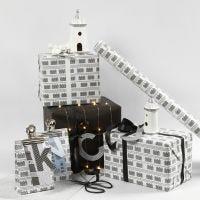 Emballage cadeau noir et blanc décoré de maisons claires et de guirlandes de lumière