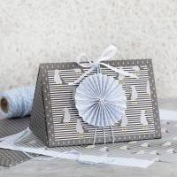 Une boîte cadeau bleu noir, décorée d'une rosette bleue et de papier design