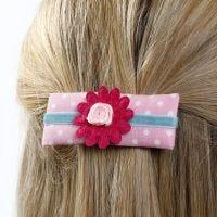 Une barette faite avec du papier cartonné décoré de tissu, ruban et de fleurs en tissu