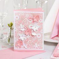 Une invitation décorée de papier cartonné à motif dentelle et de fleurs poinçonnées avec un effet 3D