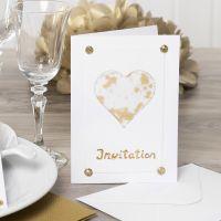 Une invitation décorée avec un coeur en papier vélin, des paillettes, des pierres de strass et du film décoratif