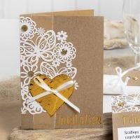Une invitation décorée avec du papier cartonné à motif dentelle, un coeur en film décoratif et des pierres de strass