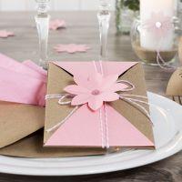 Une invitation avec des volets, fermée avec un cordon de coton et décorée d'une fleur poinçonnée