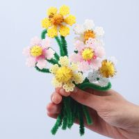 Des fleurs faites avec des perles à repasser Nabbi, des fils chenille et des pompons