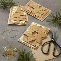 Des cartes de Noël décorées avec des décorations à suspendre en papier imitation cuir