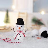 Le lutin fait un bonhomme de neige dehors, devant sa porte d'entrée