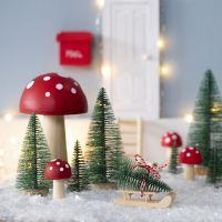 Le lutin  place un sapin de Noël devant sa porte d'entrée