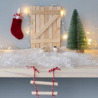 Une porte de lutin faite avec des bâtons de glace avec une échelle de corde et une boîte aux lettres de Noël