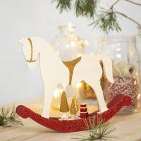 Un cheval à bascule avec de petits accessoires en bois décoré avec de la peinture acrylique, des paillettes et des perles